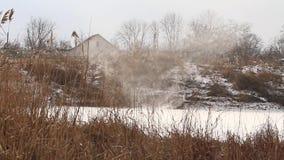 Schneesturm über einem See auf den Stadtränden des Dorfs stock video footage