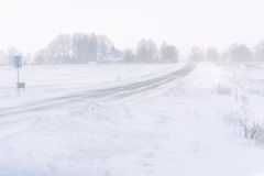 Schneesturm auf einer Landstraße im Tageslicht Stockfoto