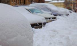 Schneesturm in der Stadt Autos in einer Straße bedeckt von einem Schnee Stockbilder
