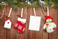 Schneetannenbaum, Fotorahmen und Weihnachtsdekor auf Seil über Rus stockfotos