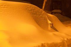 Schneewehe auf Auto nach Schneefällen in der Nachtstadt Stockfotografie