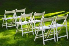 Schneeweiße Holzstühle für Gäste an einer Heiratszeremonie im Freien stockfotografie