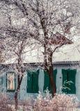 Schneewinter in der Stadt Altes ruiniertes Haus, blaue Wand und Grün schlossen Jalousie Stockbilder