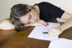 Attraktiver Mädchensekretär schlafend auf ihrem Desktop stockfotos
