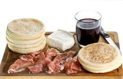 Schneidebrett mit kleinem rundem flachem Brot, Schinken, Käse und Glas Rotwein Lizenzfreies Stockfoto