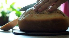 Schneiden des Brotes Ausschnitt-Scheibe des Hauptbrotes auf hölzernen Brettern schnitt das Brot mit einem Messer-Schnitt, Nahaufn stock video footage