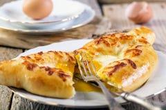 Schneiden Sie Adjara-khachapuri Gebäckkuchen mit Käse auf hölzernem Hintergrund Stockbild
