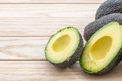 Schneiden Sie Avocado auf einer hölzernen Tabelle Stockbild
