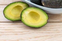 Schneiden Sie Avocado auf einer hölzernen Tabelle Stockfotografie