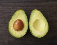 Schneiden Sie Avocadohälften mit Samen Stockfotografie