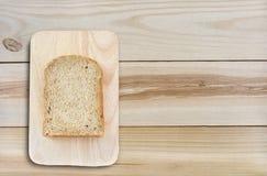 Schneiden Sie Brot mit hackendem Brett auf hölzerner Tabelle Stockfotos
