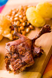 Schneiden Sie das Stücke gekochte guine Schweinfleisch, das auf Holzoberfläche nahe bei Kartoffeln, tostados und Schüssel Salsa l lizenzfreie stockfotos