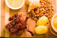 Schneiden Sie das Stücke gekochte guine Schweinfleisch, das auf Holzoberfläche nahe bei Kartoffeln, tostados und Schüssel Salsa l stockfotos
