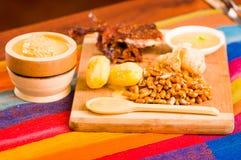 Schneiden Sie das Stücke gekochte guine Schweinfleisch, das auf Holzoberfläche nahe bei Kartoffeln, tostados und Schüssel Salsa l lizenzfreie stockfotografie