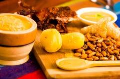 Schneiden Sie das Stücke gekochte guine Schweinfleisch, das auf Holzoberfläche nahe bei Kartoffeln, tostados und Schüssel Salsa l stockbild