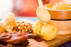 Schneiden Sie das Stücke gekochte guine Schweinfleisch, das auf Holzoberfläche nahe bei Kartoffeln, tostados und Schüssel Salsa l lizenzfreies stockbild