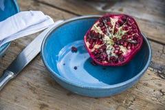 Schneiden Sie Granatapfel auf blauem Gedeck Stockfotos