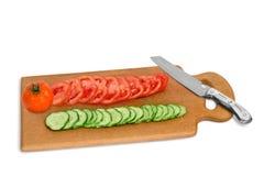 Schneiden Sie Gurke und Tomate auf dem hölzernen Brett Stockfoto