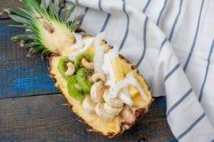 Schneiden Sie in halbe Ananas mit Kokosnuss, chia, Kiwi, Acajoubaum Stockbilder