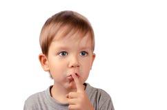 Schneiden Sie Jungenvertuschungen sein Mund mit dem Finger Stockbild