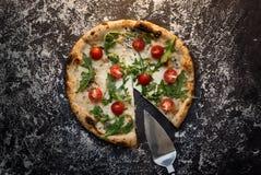 Schneiden Sie Käsepizza mit Schaufelmehl auf Draufsicht des dunklen konkreten Hintergrundes Lizenzfreie Stockfotos