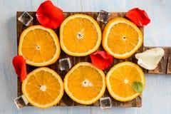 Schneiden Sie Orangen mit den Blumenblättern von Rosen und von Eis Stockfotografie