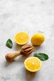 Schneiden Sie Orangen und hölzernen Juicer auf Draufsicht des konkreten Hintergrundes Stockbilder