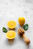 Schneiden Sie Orangen und hölzernen Juicer auf Draufsicht des konkreten Hintergrundes Stockfotografie