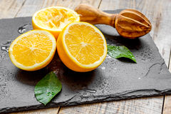 Schneiden Sie Orangen zur Hälfte und Juicer auf hölzernem Hintergrund Lizenzfreies Stockbild