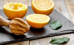 Schneiden Sie Orangen zur Hälfte und Juicer auf hölzernem Hintergrund Lizenzfreie Stockbilder