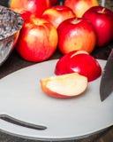 Schneiden Sie rote Äpfel mit Messer Lizenzfreies Stockbild
