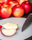 Schneiden Sie rote Äpfel mit Messer Stockfotos