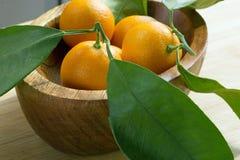 Schneiden Sie in Scheiben der Fruchtjapanischer orange in einer hölzernen Platte Stockfotografie