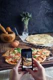 Schneiden Sie in Scheiben köstliche Pizza auf Holztisch Lizenzfreie Stockbilder