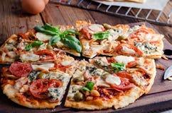 Schneiden Sie in Scheiben köstliche Pizza auf Holztisch Stockbild