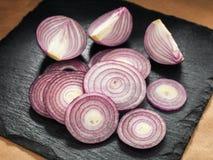 Schneiden Sie sliked Zwiebel auf einem Küchenbrett Lizenzfreie Stockfotografie