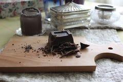 Schneiden Sie in Stückchen dunkle Schokolade auf hölzernem Brett Stockfotos