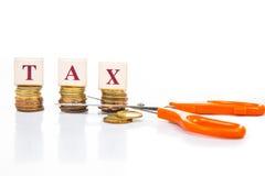 Schneiden Sie Steuerkonzept mit Münzen und Scheren stockfotos