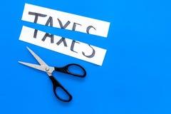 Schneiden Sie Steuerkonzept Sciccors schnitt Papier mit Wort Steuern auf blauem Draufsicht-Kopienraum des Hintergrundes stockbild