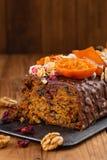 Schneiden Sie traditionellen Weihnachtsfrucht-Kuchenpudding in der Schokoladenglasur lizenzfreies stockbild