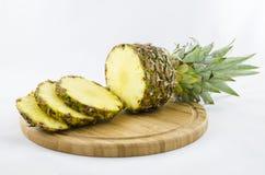 Schneiden Sie und schnitt Ananas auf dem hölzernen Brett, das auf Weiß lokalisiert wird Lizenzfreie Stockbilder