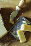 Schneiden Sie vom Parmesankäse ein Messer und die Käsereibe stockfotografie