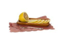 Schneiden Sie Zitrone auf der Platte mit Tafelsilber auf einer Serviette an Stockfotos