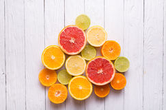 Schneiden Sie Zitrusfrüchte auf einem Hintergrund von weißen Brettern Stockfoto