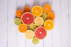 Schneiden Sie Zitrusfrüchte auf einem Hintergrund von weißen Brettern Stockbild