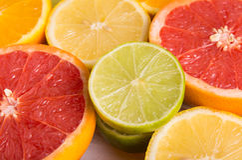 Schneiden Sie Zitrusfrüchte auf einem Hintergrund von weißen Brettern Lizenzfreie Stockfotografie