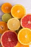 Schneiden Sie Zitrusfrüchte auf einem Hintergrund von weißen Brettern Lizenzfreies Stockbild
