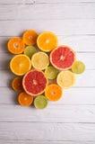 Schneiden Sie Zitrusfrüchte auf einem Hintergrund von weißen Brettern Stockbilder