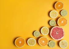 Schneiden Sie Zitrusfrüchte von verschiedenen Farben auf yellowbackground Geschnittene Zitrone, Orange, Kalk und Pampelmuse Stockfotos