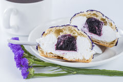Schneiden Sie zur Hälfte ein Kuchenblaubeeren-shu verzierte mit Purpurblumen O Stockfotografie